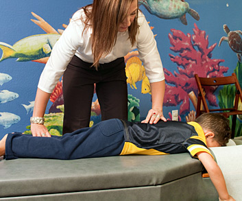 Chiropractor working on boys spine