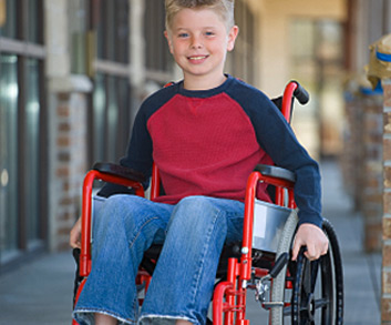 boy smiling while sitting in wheelchair